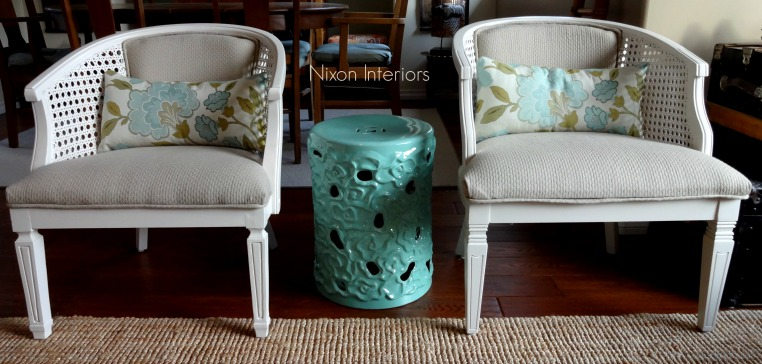 painted white reupholstered french cane barrel chirs in neutral material modern styling with ceramic asian inspired stool