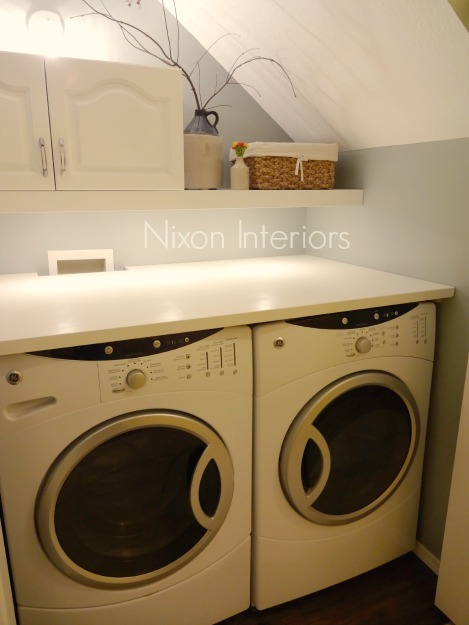 Under the stairs laundry closet painted in Benjamin Moore Raindance with white accessories