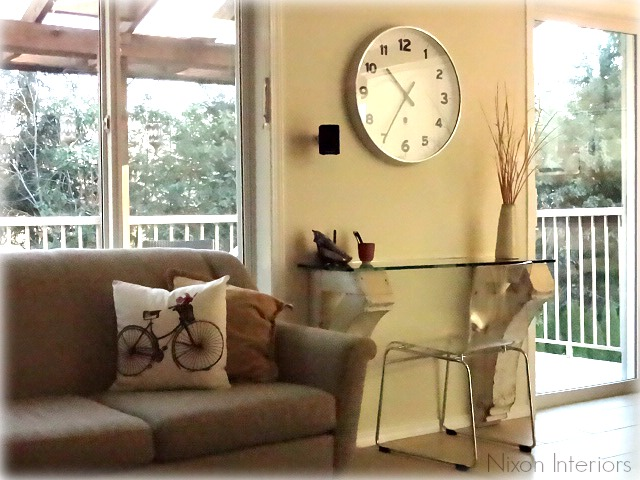 corbel desk with large wall clock and glass desk top and lucite chair