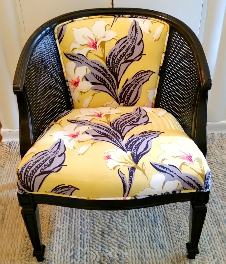 vintage cane barrel chair painted black and covered in a vintage floral