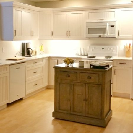 updated white kitchen with rubbed bronze handles and weathered kitchen island